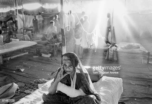 An old woman sits quietly on her bed in an emergency hospital set up by aid agencies in Anjar India after the earthquake of 2001