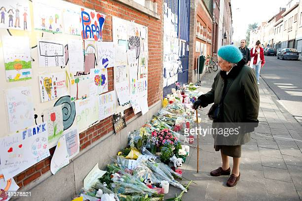 An old woman stands in front of a tribute for the victims at the entrance of the primary school SintLambertusschool in Heverlee on March 15 2012...