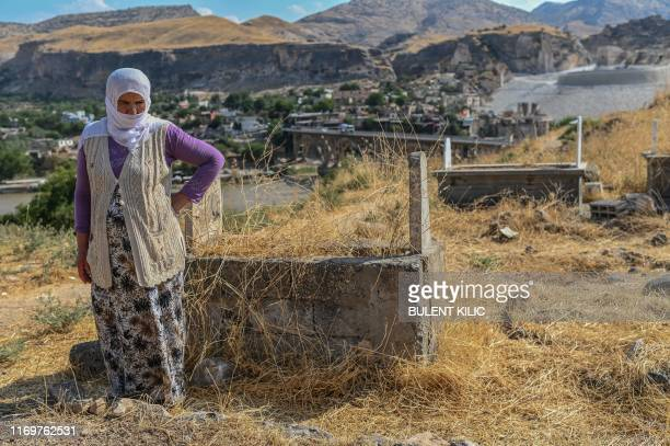 An old woman stands next her son's grave who died in 1997 at the age of 15 in an accident in Hasankeyf as she waits for workers to remove his body...