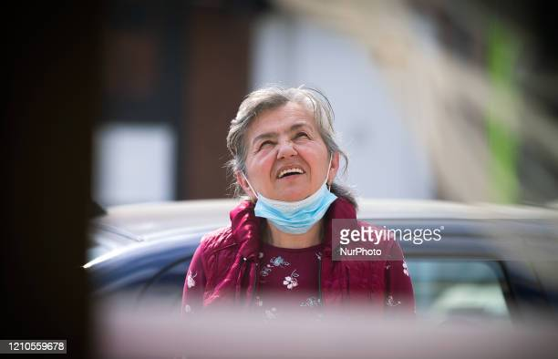An old woman takes off her mask to speak during the third day of Orthodox Easter during a curfew imposed to prevent the spread of coronavirus disease...