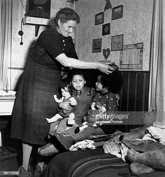 An old woman taking care of two mulattos German kids Germany 1950s