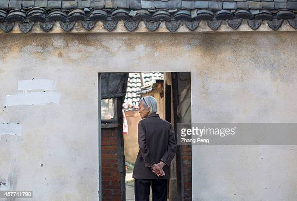 STREET NANJING JIANGSU CHINA An old woman walks back to her old house in ancient Gaochun street In China there are more than 200 million old people...