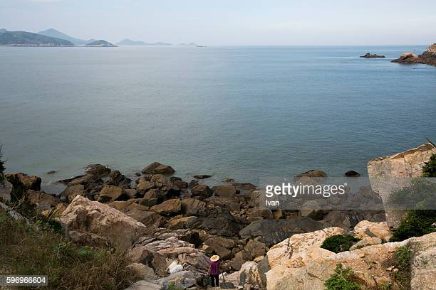 An Old Woman Wear Hats Stands on the Rock in Fornt of Ocean