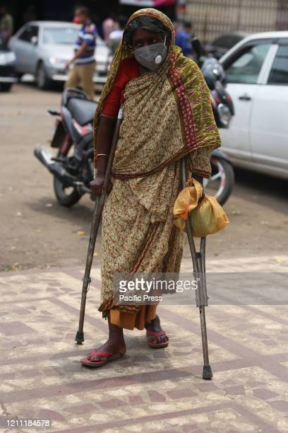 An old woman wearing a face mask is seen on the street walking with crutches People who live in the streets of Dhaka city are in the most vulnerable...