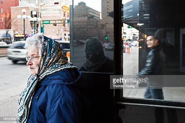 CONTENT] An old woman wearing a headscarf waits for a bus on a busy street downtown She is reflected ina stone pillar A blurred man walks by in the...