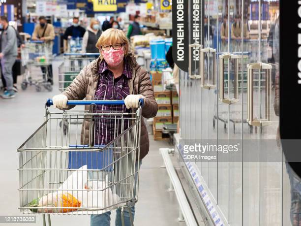 An old woman wears a face mask and hand gloves as a preventive measure at the hypermarket during the coronavirus crisis. The government has relaxed...