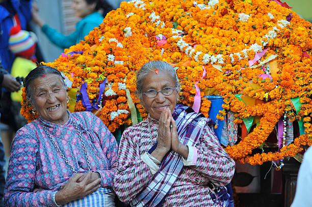 an old woman welcome by saying namaste during the celebration of mahalaxmi festival at balambu