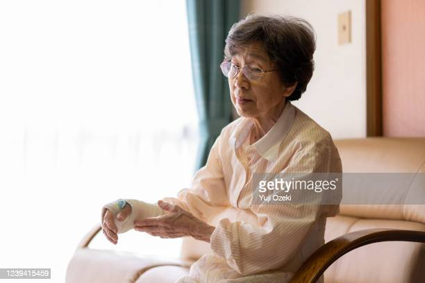 an old woman who has a broken wrist and is being treated at home - cut wrists stock pictures, royalty-free photos & images