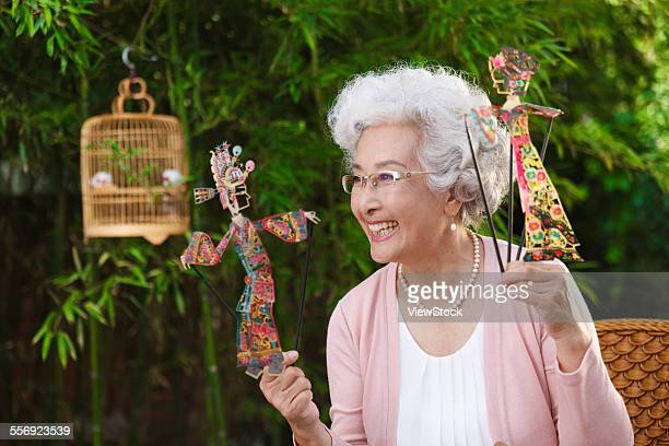 an old woman with a shadow puppet - shadow puppeteer stock photos and pictures