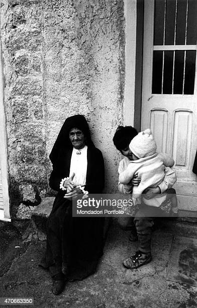 'An old woman with a traditional black dress sitting in front of her house door near her grandchildren Ollolai Italy January 1967 '