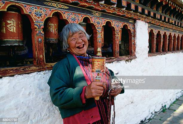 An old woman with prayer wheels laughing at the Kyichu Buddhist Temple in Paro Bhutan