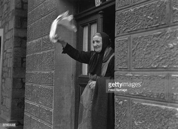 An old woman with tears in her eyes waving a white flag as the 2nd Armoured Division US 9th Army enters Lemgo