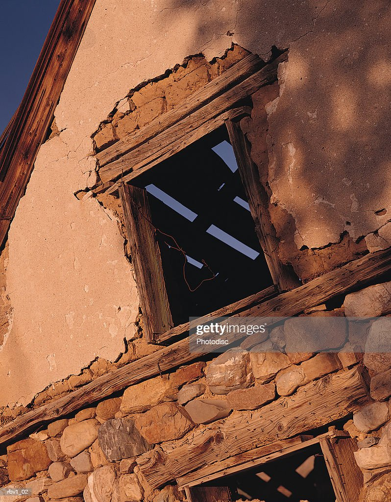 an old wooden and stone building with its window showing a ceiling that_s falling apart : Foto de stock