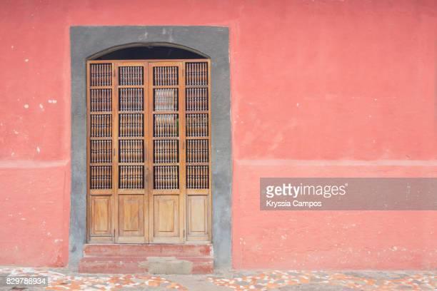 An old wooden door and colorful walls in Granada, Nicaragua