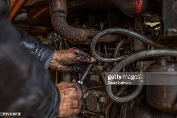 機械を修理する古いアメリカのトラック運転手 - 農業機械 ストックフォトと画像