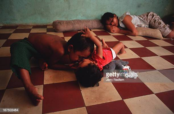 An older boy rubs noses with a younger girl while playing at the Chea Sim orphanage as their caretaker takes a nap There are 55 small children and so...