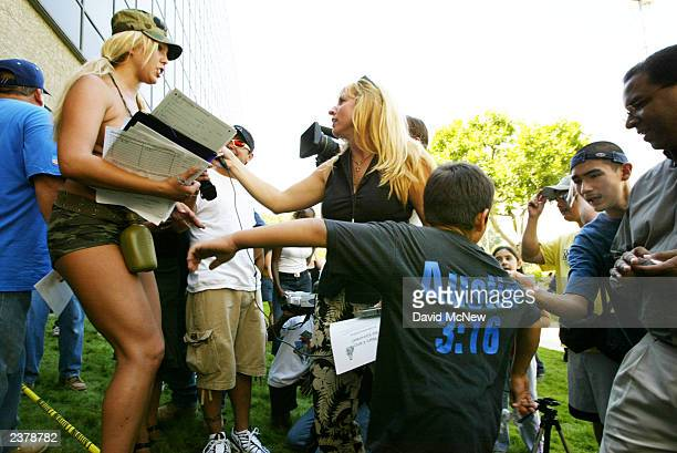 An older brother pulls sixyearold Christian Penilla away from porn star Mary Carey who talks to a reporter while gathering signatures for a run in...