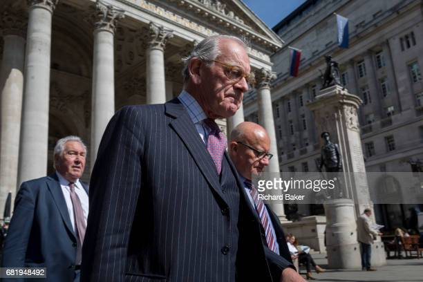 An older businessman walks with others below the classical architecture of Royal Exchange and the WW1 war memorial at Bank Triangle on 10th May 2017...