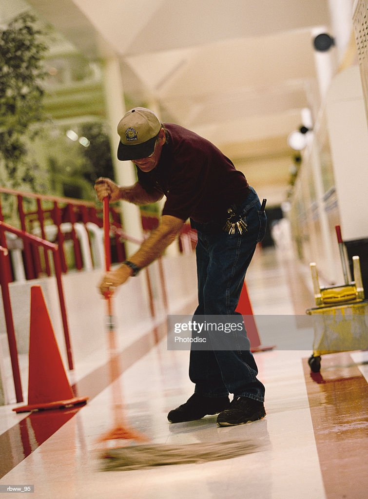 an older caucasian male janitor mops the floor of a hallway : Foto de stock