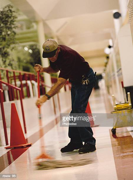 an older caucasian male janitor mops the floor of a hallway