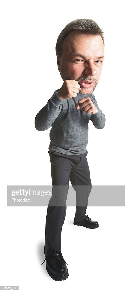 an older caucasian man looks agrily towards the camera and has his fists poised to fight : Stockfoto