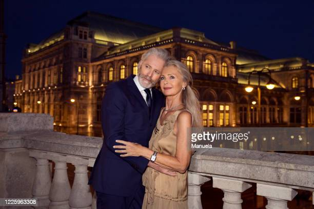 an older couple arm in arm by a balustrade during an evening out in vienna. - goed gekleed stockfoto's en -beelden