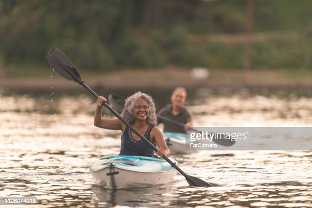 an older couple enjoy a late evening of kayaking on the river - kayak stock pictures, royalty-free photos & images