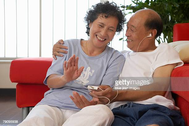 An older couple listen to music together at home.