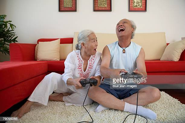 An older couple plays video games together at home.