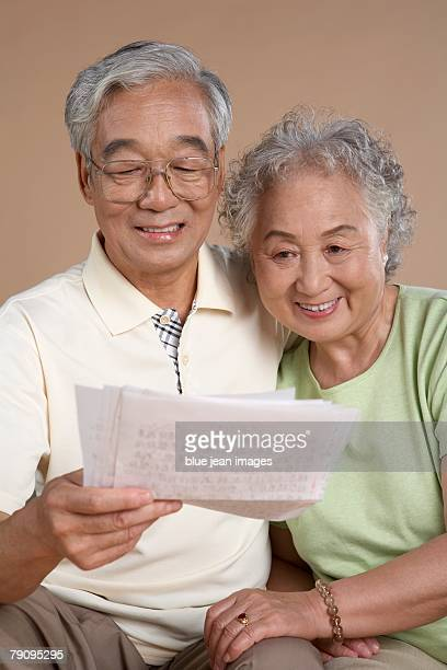 an older couple reading a handwritten letter. - asian granny pics stock photos and pictures
