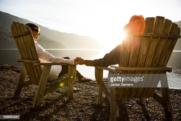 An older couple relaxing near a lake.