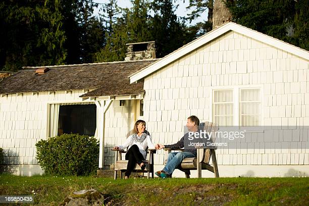 An older couple sitting near a lake.