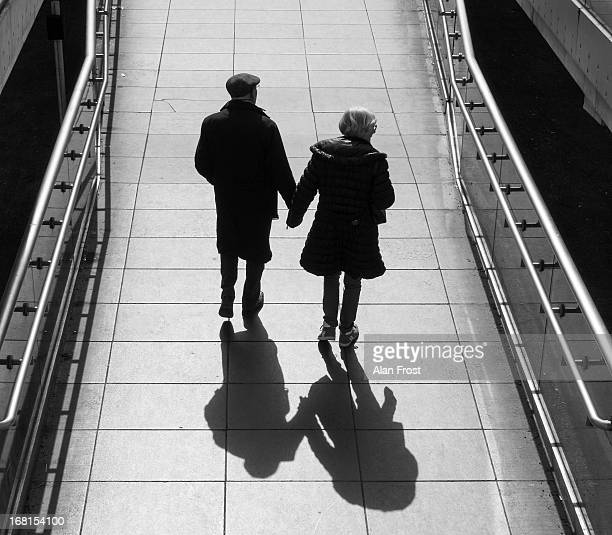 An older couple walk hand in hand up the slope leading to The Millenium Bridge in London, England. The couple are in silhouette and their shadow...