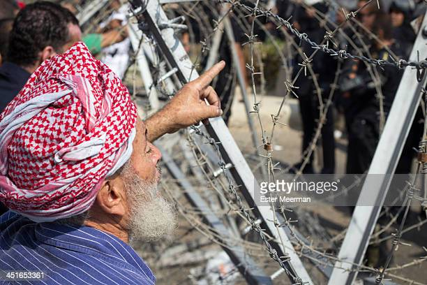 CONTENT] An older Egyptian man points his finger at Egyptian riot police standing guard behind barbed wire Supporters of ousted president Mohamed...