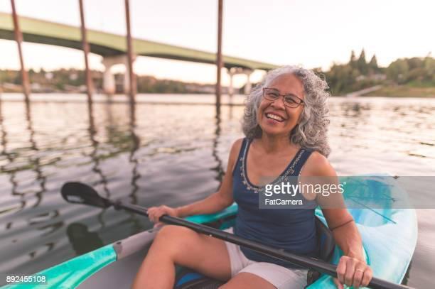 An older ethnic woman enjoys an evening of river kayaking