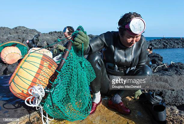 An older Korean diving woman prepares to carry her nets home on Jeju Island, South Korea.