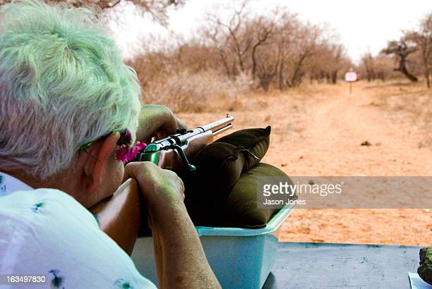 An older lady prepares to shoot a rifle at a target at a game farm in Thabazimbi, South Africa