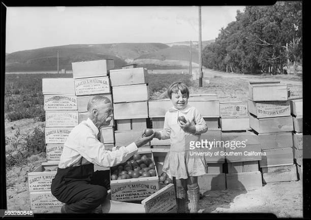 An older man hands a smiling child a tomato Camarillo California dw94~10