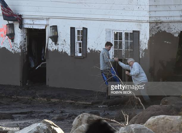 TOPSHOT An older man is hekled as he tries to enter his muddamaged home January 10 2018 in Montecito California Rescuers used dogs and helicopters to...