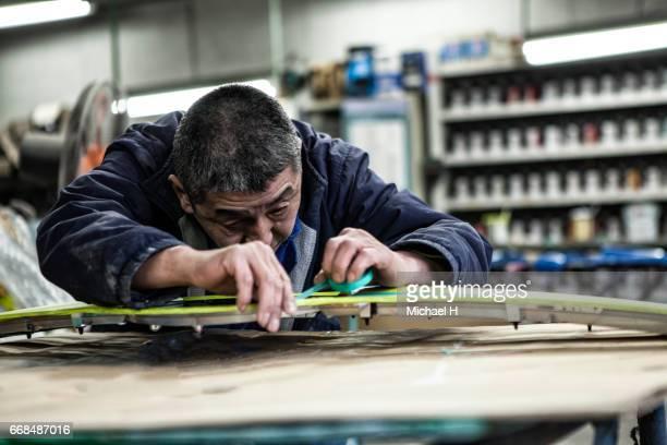 An older man painting car parts