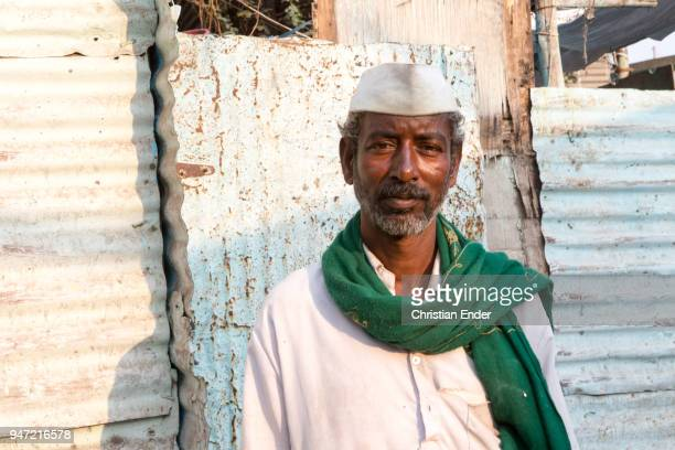 An older man with a green scarf and a traditional headgear in front of a shanty in a poor village on March 28 2013 in Bijapur India Around 50000...