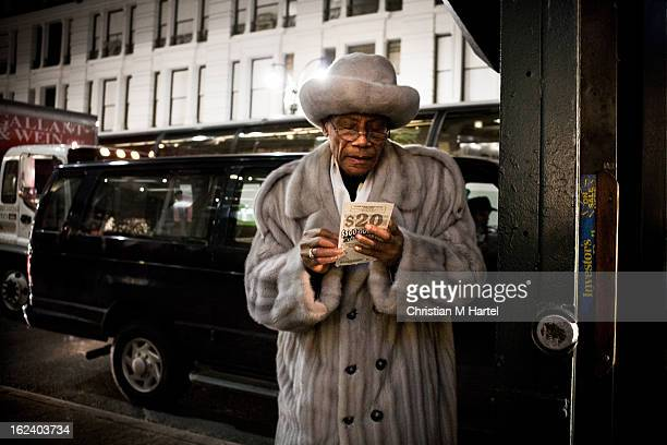 CONTENT] An older man with glasses in a fur coat and fur hat scratching off a $20 lottery ticket a sticker next to him say investor's on sale 34th...