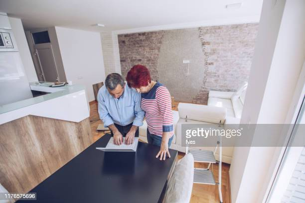 an older married couple is moving into a new apartment - borrowing stock pictures, royalty-free photos & images