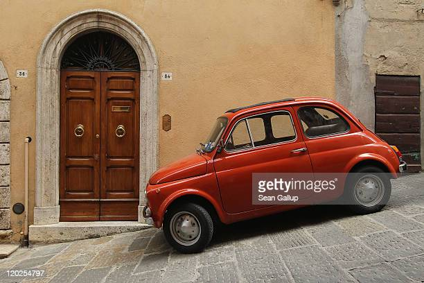 An older model Fiat stands parked on a steep incline on July 18, 2011 in Montalcino, Italy. Tuscany is among Italy's most popular tourist...