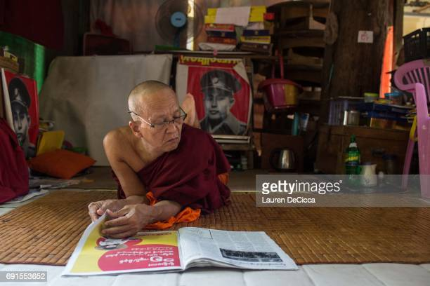 An older Monk reads a newspaper in front of a poster of General Aung San father of Aung San Suu Kyi at the Masoeyein Monastery on June 1 2017 in...