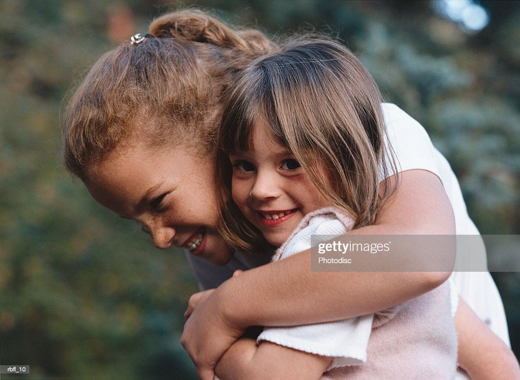 an older sister gives her baby sister a big hug : Stockfoto