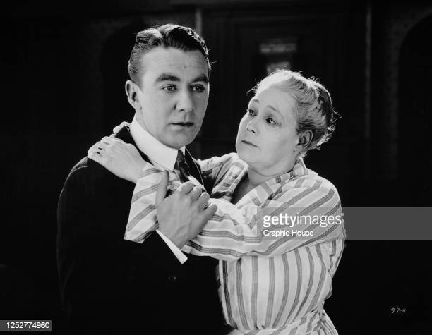 An older woman comforts an anxious young man played by IrishAmerican actor Tom Moore in a scene from a film circa 1920