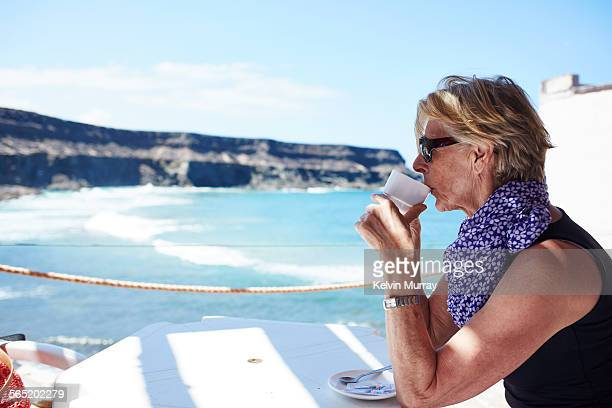 An older woman drinks a coffee with beach behind.