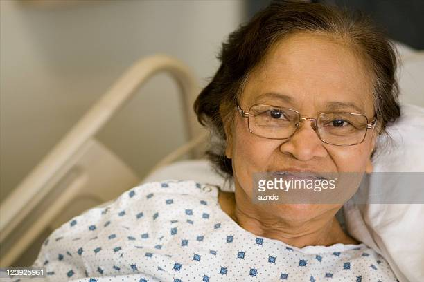 an older woman in a hospital gown laying on a bed  - indigenous culture stock pictures, royalty-free photos & images