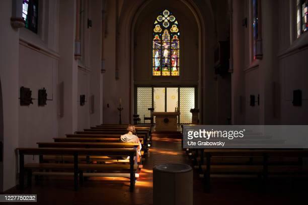 An older woman is sitting in the catholic church, Maria Meeresstern, on July 15, 2020 in Borkum, Germany.